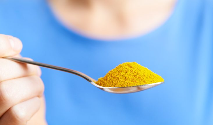 Close Up Of Woman With Spoonful Of Tumeric Powder